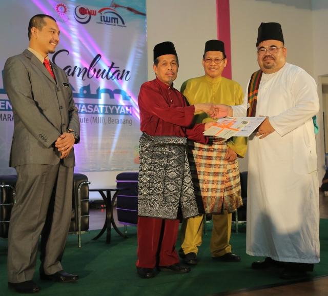 YBhg. Datuk Zanudin bin Ab Rahim (dua dari kiri) menyampaikan hadiah Juara Pertandingan Nasyid Peringkat MARA sempena Sambutan Awal Muharam MARA 2015