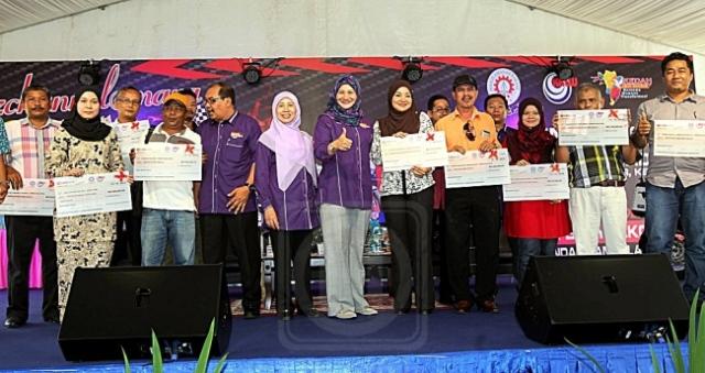 SURAYA YAACOB (tujuh dari kiri) bersama para usahawan Mara yang menerima cek pembiayaan perniagaan dalam majlis penutupan Biz Channel@ Mara Karnival Permotoran Kedah 2015 di pekarangan Stadium Darul Aman, Alor Setar, Kedah, kelmarin.