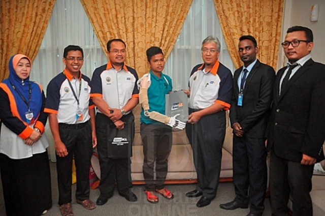 Dekan UniKL MIMET, Prof. Madya Zainorin Mohamad (tiga dari kanan) menyerahkan sumbangan khas kepada Wan Abdul Halim Wan Soor selepas dia menerima tangan mekanikal di Lumut, semalam.