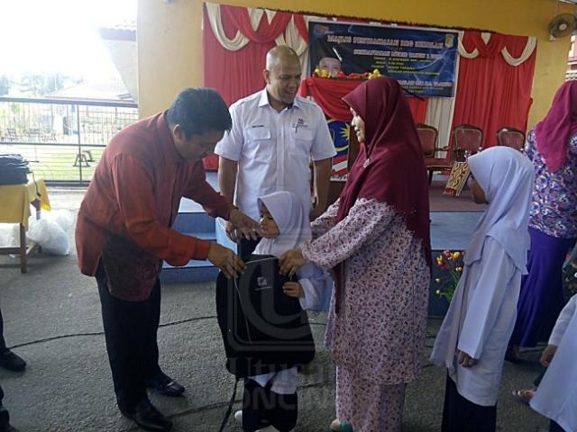 Ahmad Jazlan Yaakub menyampaikan beg sekolah kepada murid-murid dalam Program Sumbangan Beg Sekolah di Sekolah Kebangsaan (SK) Machang 1, Machang, Kelantan, baru-baru ini.