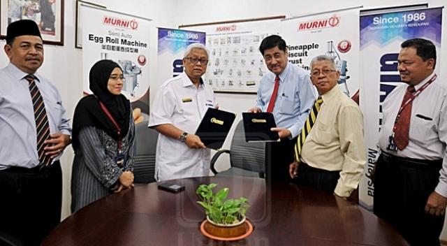 Mohd. ROSDI ISMAIL (tiga dari kiri) dan Lim Koon Ho bertukar dokumen perjanjian selepas menandatangani memorandum persefahaman antara Giatmara dan Pembekal Peralatan Bakeri Murni di Kuala Lumpur, semalam. utusan/SAIFUL BAHARI ASHARI