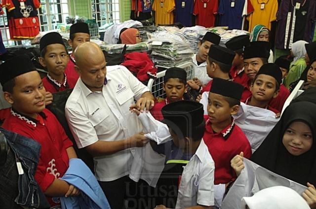 ABDUL KARIM MUSTAFA (dua dari kiri) membantu menyarungkan pakaian sekolah kepada seorang anak yatim dari Darul Kifayah Batu Caves di sebuah pusat pakaian di Kuala Lumpur, semalam.