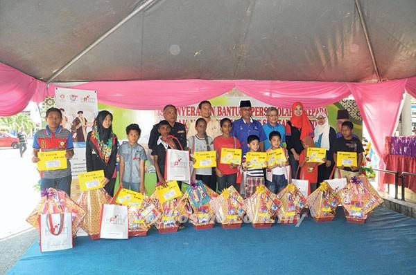 HIN YANG (barisan belakang, tiga dari kanan) bergambar dengan para pelajar yang menerima sumbangan daripada Pasar raya TF Value Mart dan KPTM di pasar raya berkenaan di Jerantut, Pahang baru-baru ini.