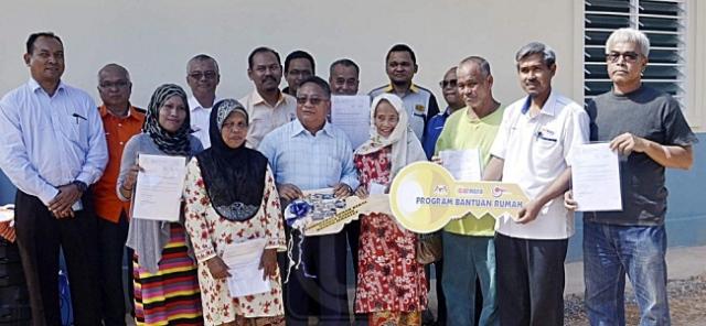 AHMAD SHUKRI ISMAIL (depan, tiga dari kiri) bersama penerima selepas majlis penyerahan replika kunci rumah di Kampung Bukit Rang, Jerantut, Pahang, semalam. Utusan/HARIS FADILAH AHMAD
