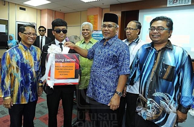 Ahmad Nazlan Idris (dua dari kanan) memasukkan sampul berisi wang ke dalam tabung sebagai gimik Pelancaran Tabung Kebajikan Mahasiswa Kolej Poly-Tech Mara Kuala Lumpur, di Kuala Lumpur, semalam.