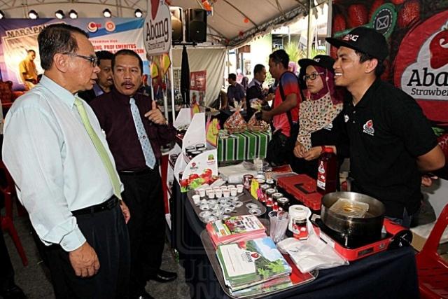 ABU AZAM MD. YASSIN (kiri) diberi penerangan oleh Kamaruddin Awang (dua dari kiri) ketika melawat pameran Festival Mini Makanan Mara Pahang 2016 di Kuantan, kelmarin. Utusan/AHMAD ZAKKI JILAN