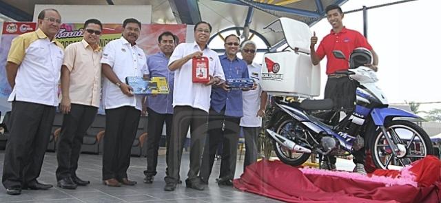 Ismail Sabri Yaakob (lima dari kiri) melancarkan program Usahawan Bergerak untuk belia dalam Majlis Perasmian Karnival Program Peningkatan Pendapatan Ke Arah Menangani Kos Sara Hidup Peringkat Negeri Pahang di Bera, Pahang, semalam.
