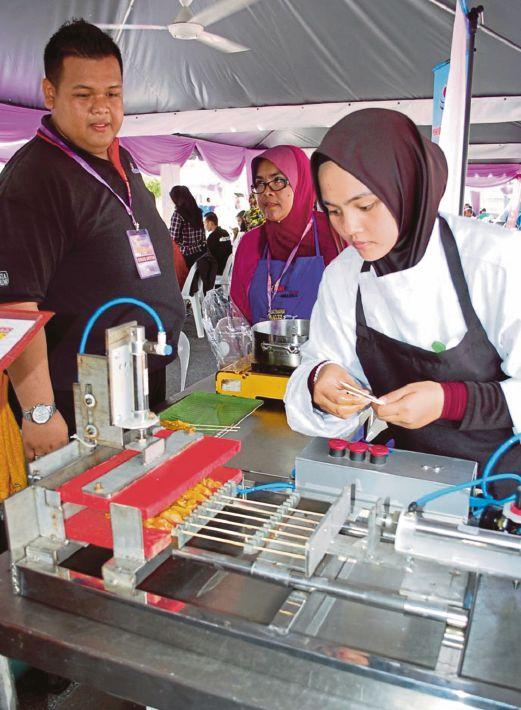 PELAJAR Pusat GiatMARA menggunakan mesin mencucuk daging pada lidi sate.