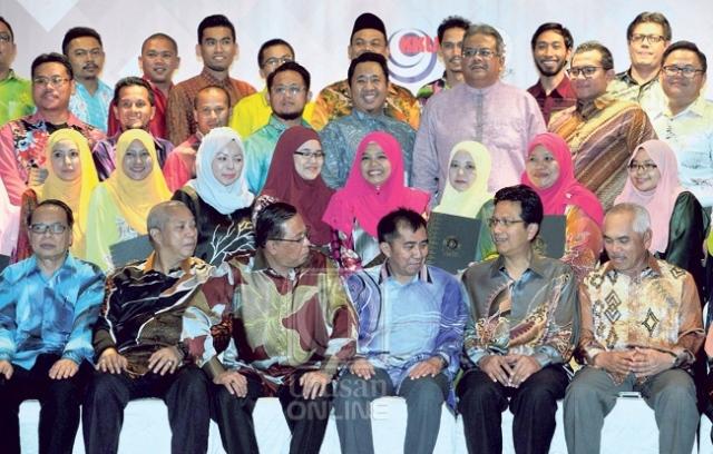 ISMAIL Sabri Yaako b (duduk tiga kiri) mengatakan sesuatu kepada pegawai Mara semasa sesi bergambar bersama sebahagian penerima anugerah dalam Majlis Anugerah Perkhidmatan Cemerlang Subsidiari Mara 2015 di Kuala Lumpur, semalam. – UTUSAN/GAIE UCHEL