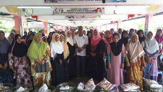 PENGERUSI Kolej Poly-tech Mara (KPTM), Ahmad Nazlan Idris (tengah) bersama ibu tunggal daerah Jerantut ketika hadir menyampaikan sumbangan Aidilfitri kepada 100 ibu tunggal dalam program Titian Kasih Parlimen Jerantut Anjuran Pertubuhan Kebajikan Ibu Tunggal Jerantut di Dewan SK Jerantut Jaya.