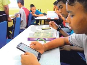 Pelatih, Muhammad Luqman Hakim A'riff, 18, memanfaatkan telefon pintar untuk menyahut kempen #MalaysiaNgaji, Rabu lalu.