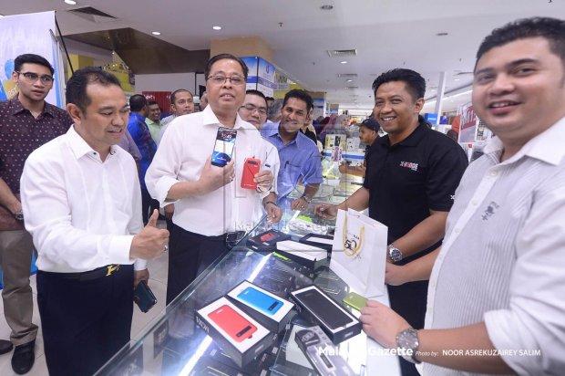 Menteri Kemajuan Luar Bandar dan Wilayah, Datuk Seri Ismail Sabri menunjukkan salah satu telefon pintar yang dijual di MARA Digital di Anggerik Mall Shah Alam baru-baru ini.