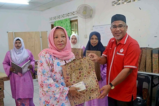 AHMAD NAZLAN IDRIS menyampaikan sumbangan kepada salah seorang ibu tunggal dalam program ziarah di Kampung Batu Embun, Jerantut, Pahang, baru-baru ini. UTUSAN/HARIS FADILAH AHMAD