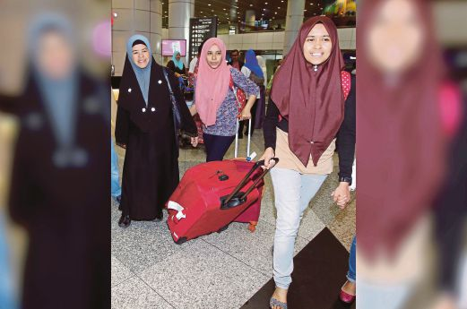 ISTERI kepada Mohamad Sahar, Hawiyah Ahmad (kanan) bersama anak mereka, Atikah (tengah) dan Amirah tiba di Lapangan Terbang Antarabangsa Kuala Lumpur (KLIA) pagi tadi. - Foto Ahmad Irham Mohd Noor