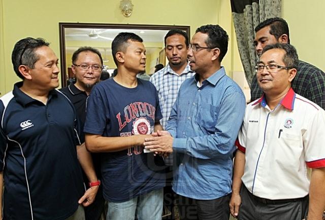 Azhar Abd. Manaf (depan, dua dari kanan) menyampaikan sumbangan kepada Mohamad Adhwa Mohamad Sahar (dua dari kanan) ketika berkunjung ke rumah Mohamad Sahar Mhd Noor di Taman Desa Melang Dua, Kuala Pilah, Negeri Sembilan semalam. UTUSAN/ASWAD YAHYA