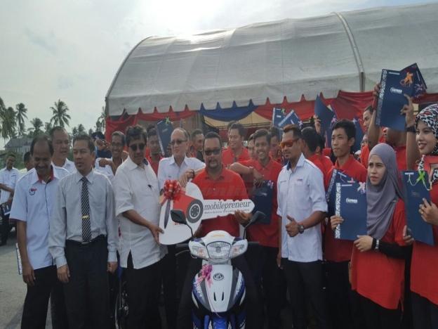 Azian menyerahkan replika kunci kepada Azmi Putera Zakaria sebagai simbolik penyerahan Mobilepreneur kepada 40 penerima di Pusat GiatMARA Indera Mahkota di sini, hari ini. - Foto Sinar Harian