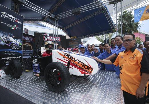 ABU Azam (kanan) melihat kereta lumba ciptaan pelajar-pelajar Kolej Kemahiran Tinggi MARA, Masjid Tanah Melaka selepas pra pelancaran IPMA Race 2017 di Tapak Ekspo MAEPS, hari ini. - Foto Sairien Nafis