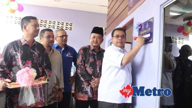 ABDUL Fattah menandatangani plak bagi perasmian Kiosk Koperasi Sekolah Menengah Kebangsaan Wakaf Bharu Tumpat. FOTO Nik Abdullah Nik Omar