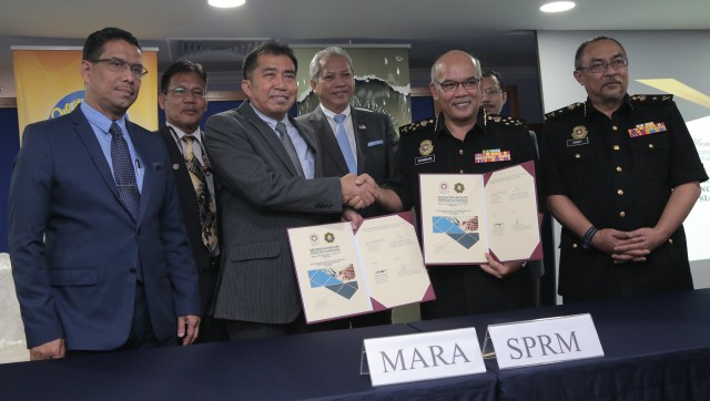 Ketua Pengarah MARA, Datuk Ibrahim Ahmad (tiga kiri) bersama Pengerusi MARA, Tan Sri Annuar Musa (tengah) bertukar dokumen memorandum persefahaman dengan Timbalan Ketua Pesuruhjaya (Pencegahan) SPRM. -foto oleh MiziBTKM