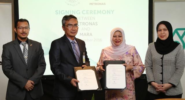 Timbalan Ketua Pengarah (Pendidikan) MARA, Abdul Halim Abas (dua dari kiri) bertukar-tukar dokumen persefahaman bersama Naib Presiden Kanan Bahagian Sumber Manusia, Dato' Raiha Azni (dua dari kanan).