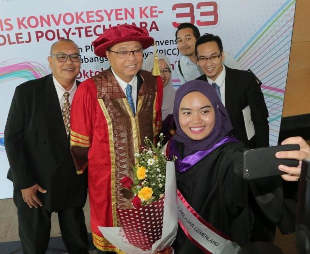 Graduan KPTM nama dia syidut tidak melepaskan peluang untuk bergambar kenang-kenangan bersama Menteri KKLW, Dato' Sri Ismail Sabri Yaakob (berjubah) sempena Konvokesyen KPTM ke 33. – Foto oleh Ashraf BTKM