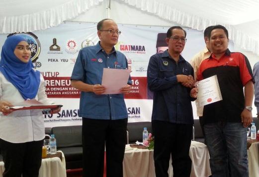 Pengerusi GiatMARA Malaysia, Datuk Azian Osman (dua kiri) menyaksikan Pengerusi Jawatankuasa Hal Ehwal Pengguna, Pembangunan Usahawan, Koperasi, Badan Bukan Kerajaan (NGO) dan Masyarakat Sivil negeri, Datuk Samsudin Abu Hassan (tiga kanan) menyerahkan Sijil Latihan 1Malaysia kepada  seorang usahawan ketika Majlis Penutup Karnival Technopreneur Perak 2016 di Dataran Angsana Mall, Greentown. - Gambar Balqis Jazimah Zahari