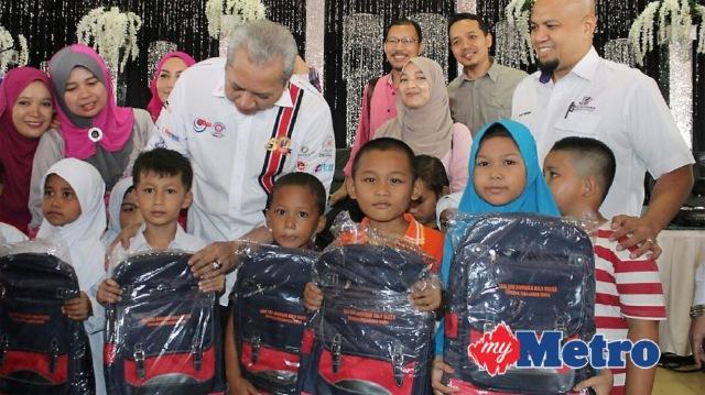 ANNUAR Musa bersama KEtua Pegawai Eksekutif Yayasan MARA, Datuk Abdul Karim Mustapha (kanan) menyampaikan sumbangan barang persekolahan kepada murid tahun satu. FOTO Nik Abdullah Nik Omar