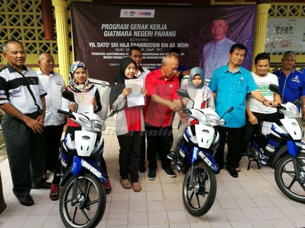 Jabar (kiri) mengiringi Shahiruddin (lima, kanan) menyampaikan enam buah motosikal Mobilepreneur kepada usahawan bidang jahitan dan elektrik GIATMARA. - Foto Sinar Harian