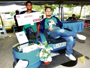 Shamsul Azhar (duduk) dan Mohd Sharif bangga menunjukkan produk yang dihasilkan oleh mereka.