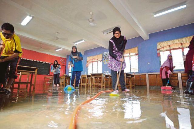 KAKITANGAN sekolah, guru dan pelajar bergotong-royong membersih kawasan yang dinaiki air di Sekolah Kebangsan Matang