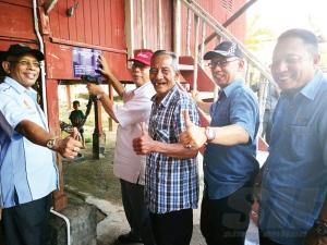 Abdullah Hasnan (dua, kiri) memasang plak projek di kediaman Bakar (tengah) yang tersenyum gembira menerima bantuan PBR sambil diperhatikan Jamal (dua, kanan).