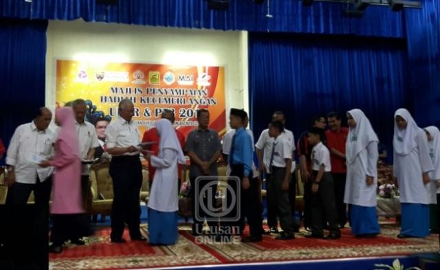 PERDANA Menteri, Datuk Seri Najib Tun Razak menyampaikan hadiah kepada murid yang cemerlang dalam Ujian Pencapaian Sekolah Rendah (UPSR) 2016 Parlimen Pekan di Dewan Konvensyen Sultan Ahmad Shah di Pekan, Pahang hari ini.-UTUSAN ONLINE