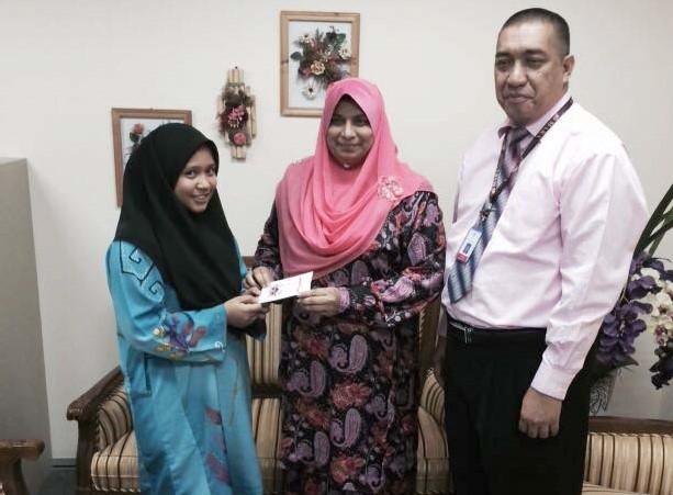 YB Datuk Normala Abdul Samad menyampaikan sumbangan peribadi kepada Norrasyiqah untuk menjelaskan yuran Checkpoint IGCSE.