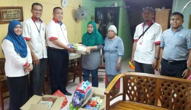 Pengetua MRSM JB (tiga dari kiri) menyampaikan sumbangan kepada keluarga pelajar