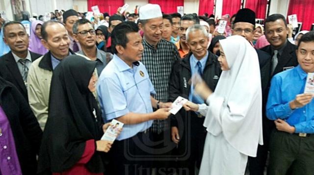 IKMAL HISYAM ABDUL AZIZ (dua dari kiri) menyampaikan sumbangan wang ihsan kepada pelajar cemerlang dalam peperiksaan PT3 di Tanah Merah, Kelantan, semalam.