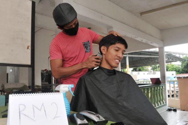 Muhammad Hafidz menggunting rambut pelanggannya Muhammad Osman Abdullah, 22, di sebuah surau ketika ditemui Bernama baru-baru ini.