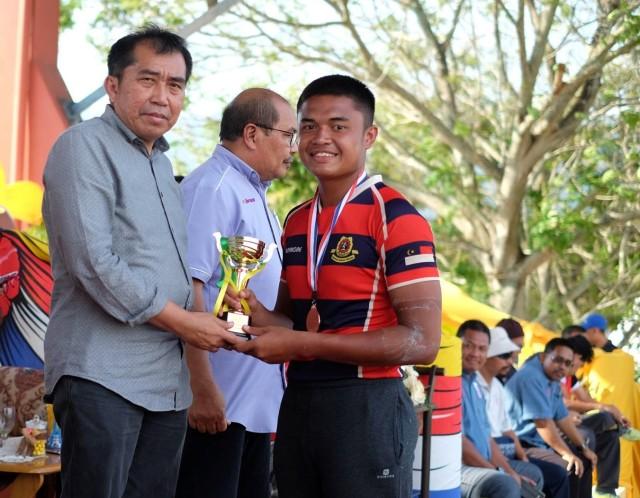Ketua Pengarah MARA (kiri) menyampaikan pingat kepada pemenang Kejohanan Rugbi